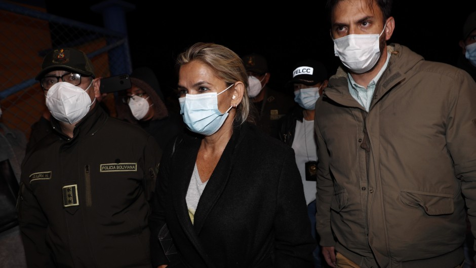 La ex presidenta de facto, Jeanine Añez, en el momento de su detención, escoltada por el ministro de Gobierno de Bolivia,  Carlos Eduardo Del Castillo y el jefe de la Policía, Jhonny Aguilera, en el aeropuerto militar de El Alto.